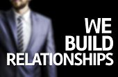 image of mans-best-friend  - We Build Relationships written on a board with a business man on background - JPG