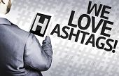 image of hashtag  - Business man with the text We Love Hashtags in a concept image - JPG