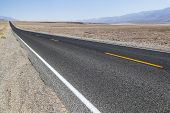 foto of long distance  - Death Valley road straight across the desert to the mountains in the distance