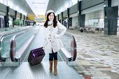 image of carry-on luggage  - Portrait of beautiful woman standing in the airport hallway while wearing winter coat and carrying luggage - JPG