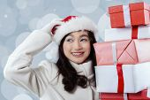 picture of scratching head  - Portrait of gorgeous girl scratching her head while wearing santa head and holding christmas gift boxes - JPG