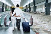 stock photo of escalator  - Two people walking on escalator while carrying a luggage in the airport hall - JPG