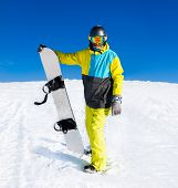picture of snowboarding  - Snowboarder hold snowboard on top of hill - JPG
