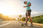 picture of skate board  - Sportive man with skate at sunset looking phone - JPG