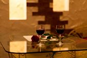 stock photo of low-light  - restaurant table red rose and glass of wine with low natural candle light - JPG