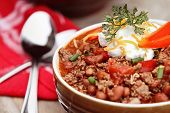 stock photo of chives  - Bowl of Chili Con Carne garnished with sour cream chives and cheddar cheese - JPG