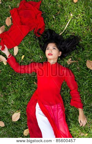 top view of Asian Woman in Red and White Ao Dai Lying Down on Grassland