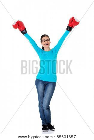 Attractive young woman wearing boxing gloves.