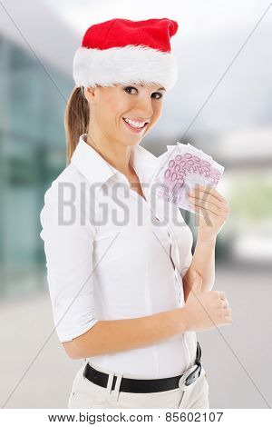 Young business woman holding money in santa hat