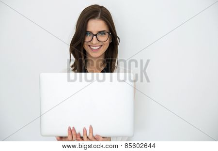 Attractive happy businesswoman standing with laptop over gray background