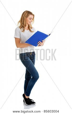 Young woman reading notes in her binder.