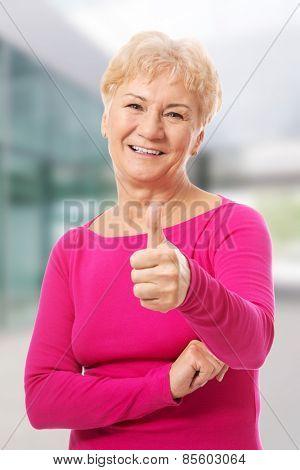 Old woman wearing pink shirt, showing OK