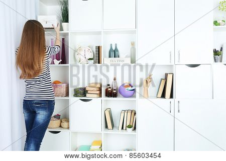 Woman looking for something in closet, in room with modern interior