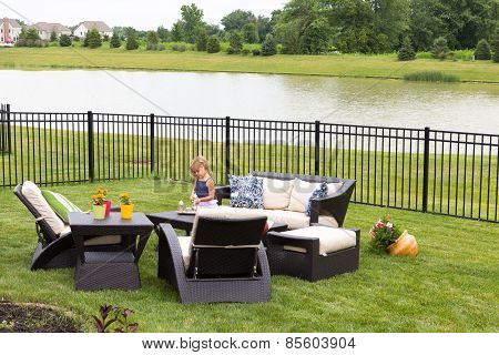 Little Girl Standing Amongst Garden Furniture