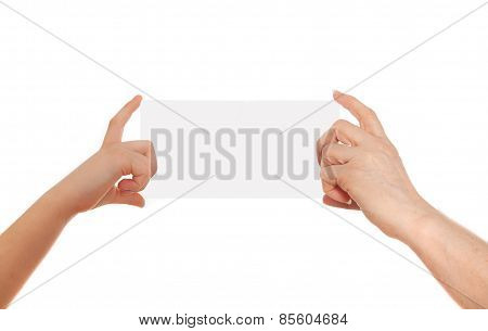 Adult's hand and child's hand holding white paper, cardboard. White background with space for text