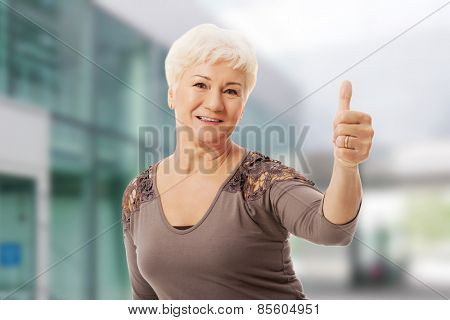 Old smiling woman showing OK