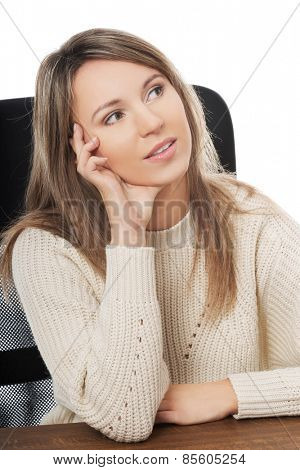 Pensive woman sitting at the desk.