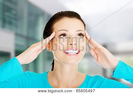 Young happy casual woman is touching her temples
