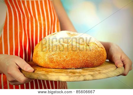 Loaf of freshly bread in female hands on wooden cutting board on light blurred background