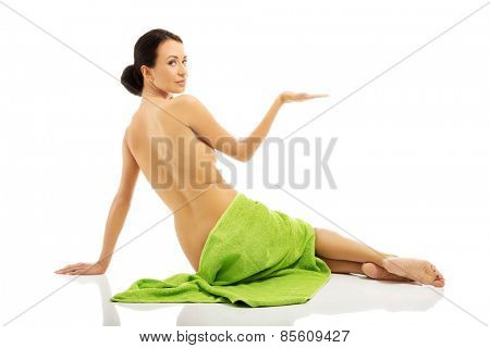 Woman wrapped in towel holding something invisible.