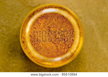 freshly grinded turmeric powder stored in a container kept on a plain background