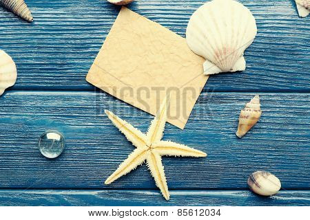 Card blank with sea star and shells on wooden background