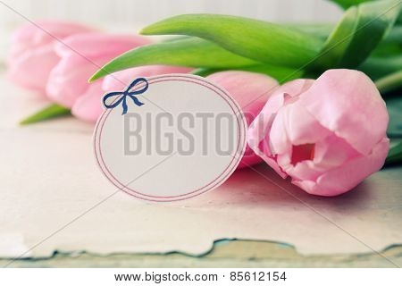 Beautiful pink tulips with tag on wooden background