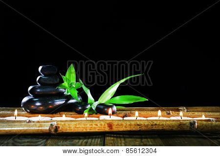 Beautiful composition with spa stones and candles on table on dark background