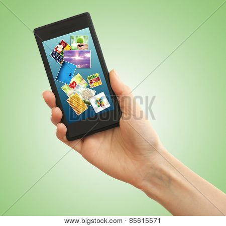 Hand holding mobile phone with different pictures on screen, green background