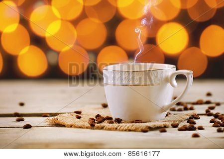 Cup of coffee on wooden table on bright background
