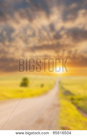 Blurred background of a sunrise through clouds over a rural road