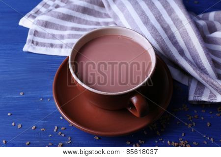 Cup of cocoa with sugar on color wooden background