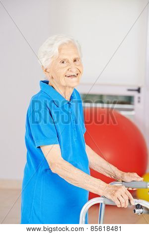 Old smiling senior woman going with walker to physiotherapy