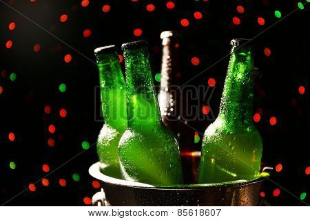 Glass bottles of beer in metal bucket on dark bright background