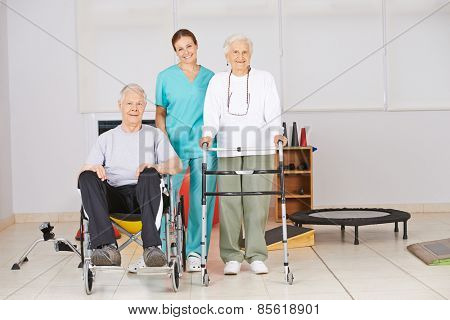 Two senior people with nurse during physiotherapy in a nursing home