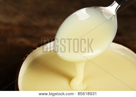 Bowl with condensed milk and spoon on table close up