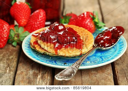 Wafers with strawberry jam and berries on plate on table close up