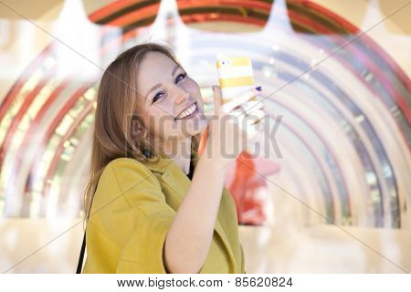 Beautiful young woman reading a message on the phone