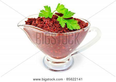 Adjika in glass gravy boat with parsley