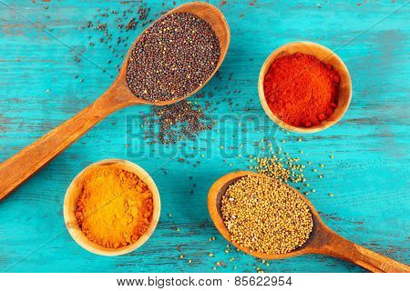 Different seasoning in wooden spoons and bowls on color wooden table background
