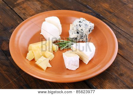 Slices of different sort of cheese on plate on wooden table background