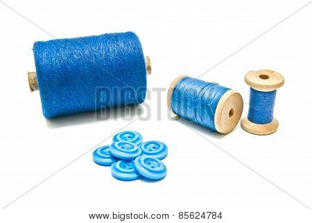 Spools Of Thread And Blue Buttons On White