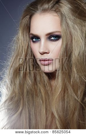 Young beautiful sexy woman with long blonde hair and smoky eyes
