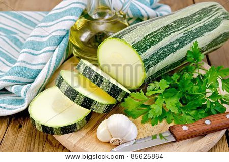 Zucchini green striped with garlic and oil on board
