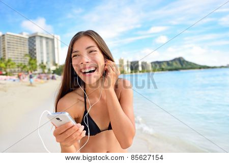 Happy beach woman listening to music on smartphone putting earphones in ears. Relaxing casual girl in bikini during summer holidays walking having fun streaming audio with wireless 4g on mobile phone.