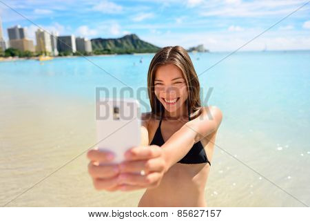 Girl taking fun selfie picture on beach vacation. Summer holiday woman happy at smartphone camera taking self-portrait on her Hawaiian travel vacations in Waikiki, Honolulu city, Oahu, Hawaii, USA.