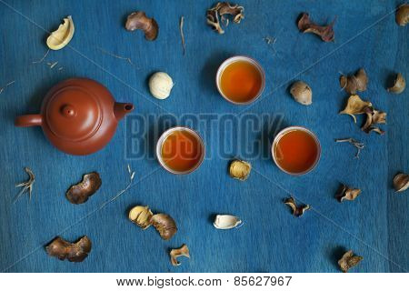 Teapot And Three Cups With Shuck On Blue Wooden Table.