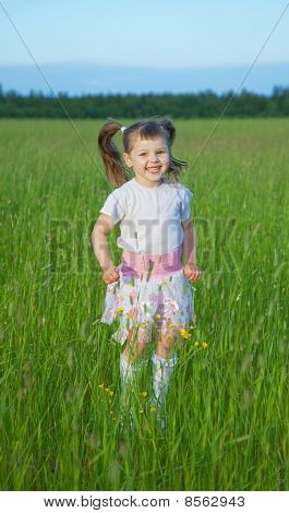 Happy Child Jumps On Green Grass In Field