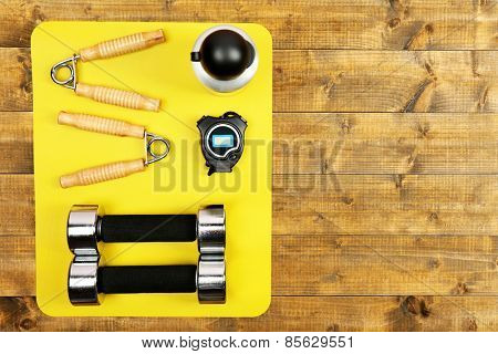 Sports equipment on mat on wooden floor, top view