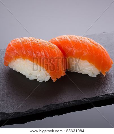 Salmon Sushi Nigiri On A Stone Plate Over Black Backround